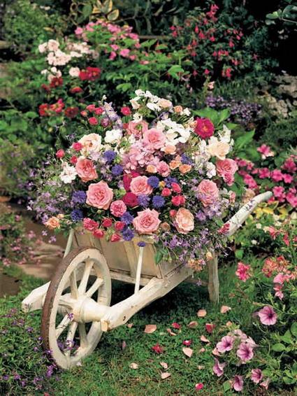 una carretilla llena de flores es una propuesta muy utilizada en aquellos jardines con estilo vintage es una buena manera de reutilizar y decorar con