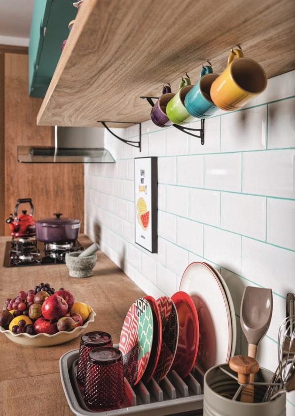 Tazas de colores colgadas de un estante en la cocina