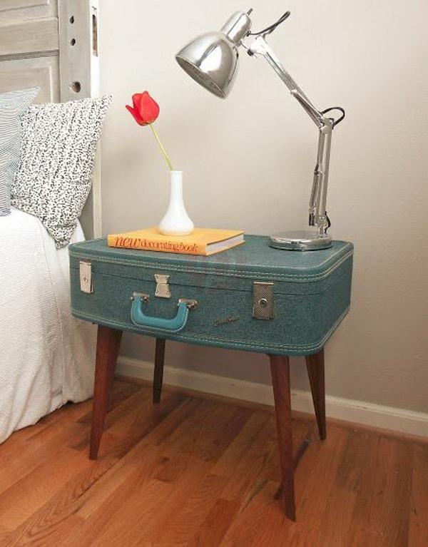 Mesa de noche con una maleta antigua